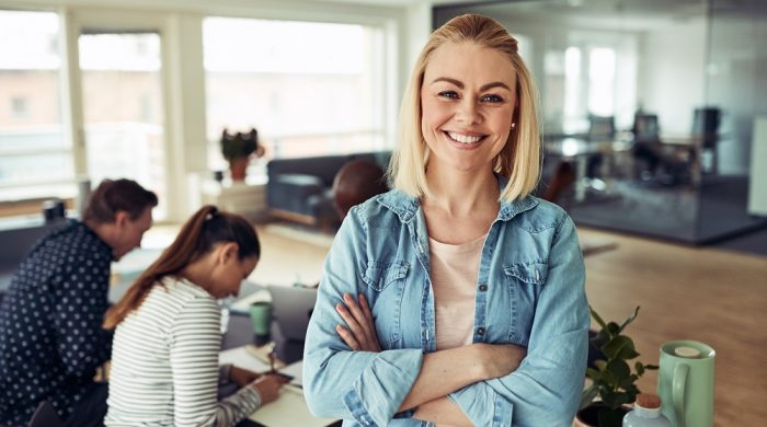 Smiling young businesswoman standing with her arms crossed in an office with colleagues working at a table in the background